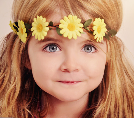 Photo for A closeup of a happy little girl wearing a yellow flower Garland on her hair for a beauty or spring concept. - Royalty Free Image
