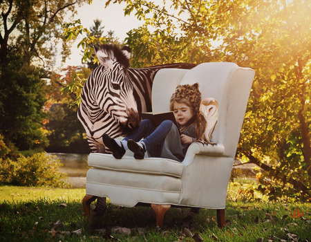 Photo for A young child is reading a book on a white chair with a zebra and owl next to her in nature for an education or creativity concept. - Royalty Free Image