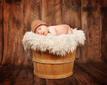 Photo pour A cute newborn baby is sleeping in a wooden basket with a wooden background and is wearing a hat for a photography portrait or love concept. - image libre de droit