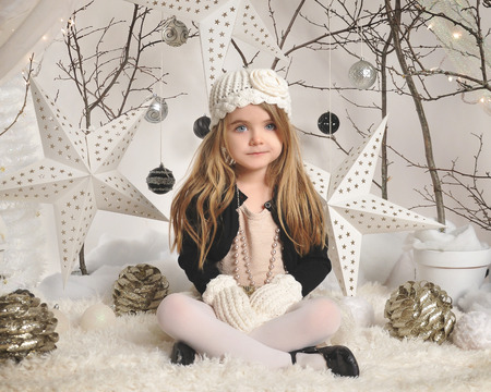 Foto de A little girl is sitting in a white winter wonderland setup with trees, hanging stars and Christmas lights in the background for a season or holiday concept. - Imagen libre de derechos