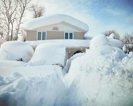 Foto de A house, roof and cars are covered with deep white snow in western new york for a weather or blizzard concept. - Imagen libre de derechos