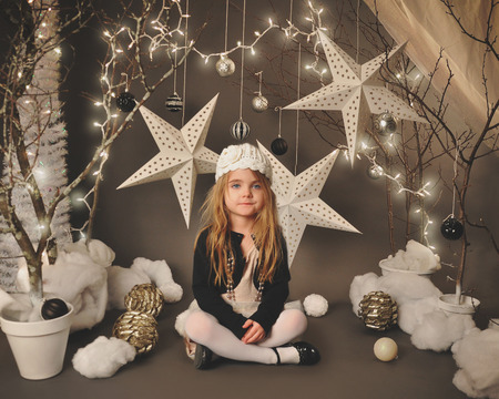 Foto de A little girl is sitting in a winter wonderland setip with trees, hanging stars and christmas lights around the background for a season or holiday concept. - Imagen libre de derechos