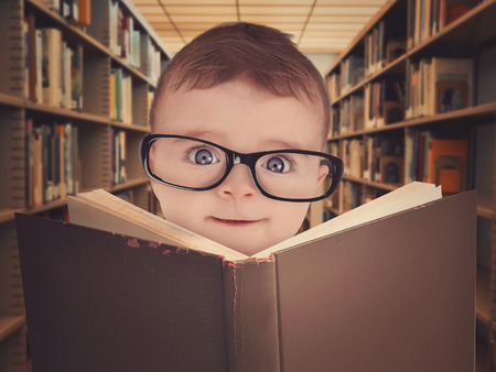 Photo pour A cute little baby is wearing eye glasses and reading a library book for an education or learning concept. - image libre de droit