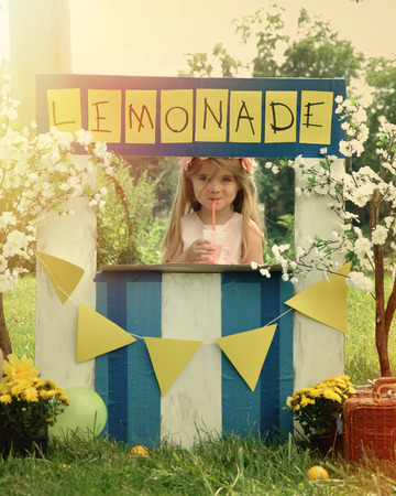 Foto de A little girl has an outdoor homemade lemonade stand with a sign and she looks happy for a small business or money concept. - Imagen libre de derechos