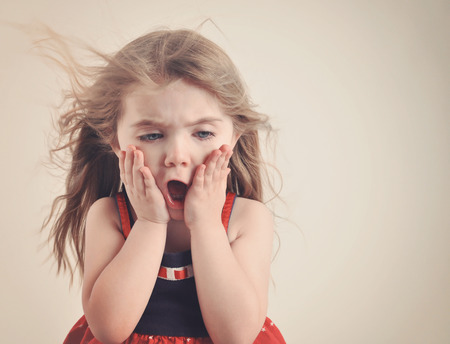 Photo pour A little girl has an open mouth with hair blowing on a retro background for a surprise or shock concept. - image libre de droit
