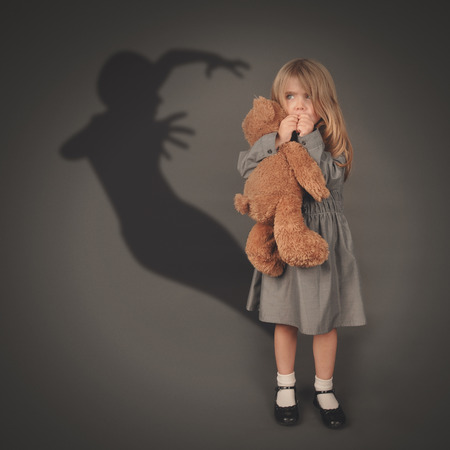 Photo pour A little girl is holding a teddy bear and looking at a scary dark silhouette of an evil ghost popping out on a gray background. - image libre de droit