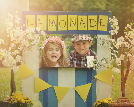 Foto de Two little kids are selling lemonade at a homemade lemonade stand on a sunny day with a sign for an entrepreneur concept. - Imagen libre de derechos