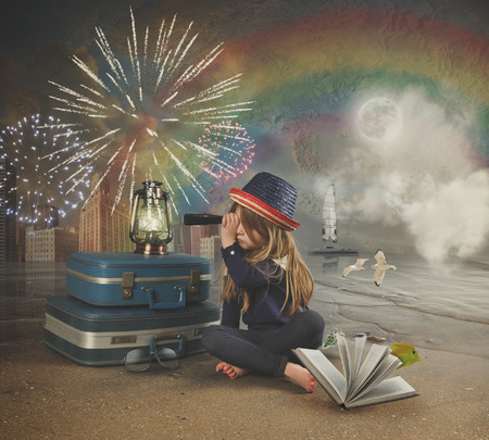 Foto de A little girl at the beach is looking through a magnifying telescope at fireworks in the sky with a map and rainbow in the background for a travel imagination concept. - Imagen libre de derechos