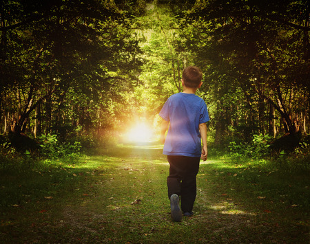 Photo pour A child is walking in the dark woods into a bright light on a path for a freedom or happiness concept. - image libre de droit