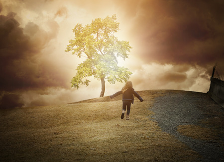 Foto de A little child is running up a hill to a glowing tree of light with dark clouds in the background. Use it for a hope, freedom or happiness concept. - Imagen libre de derechos