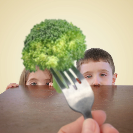Photo pour Two little kids are hiding behind a table from a fork with a healthy piece of broccoli on it for a childhood nutrition or picky eater concept. - image libre de droit