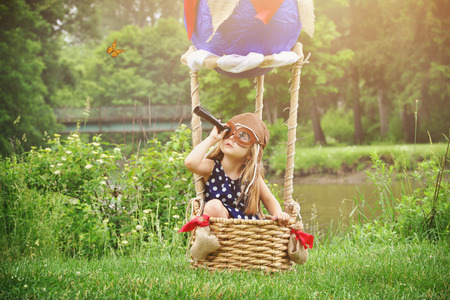 Photo pour A little girl is sittin in a hot air balloon basket in the park pretending to travel and fly with a pilot hat on for a creativity or imagination concept. - image libre de droit