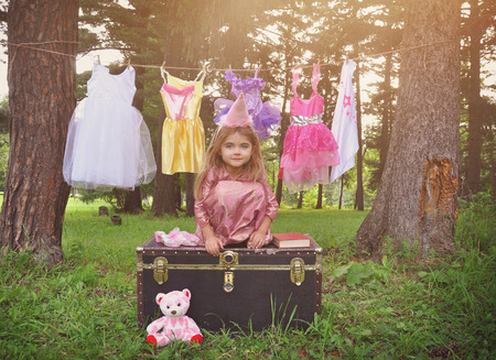 Photo for A little child is petending to be a princess outside with dressup clothes hanging on a clothesline for a imagination or creativity concept. - Royalty Free Image