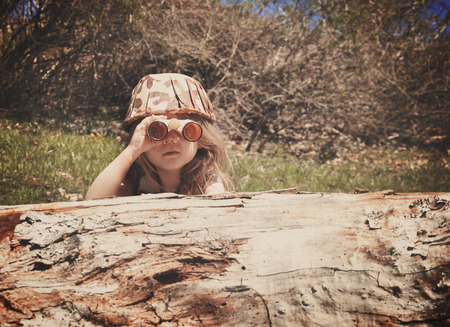 Foto de A little girl is hiding behind an old log in the woods with a camouflage hat and binoculars searching and playing for an imagination or exploration concept. - Imagen libre de derechos