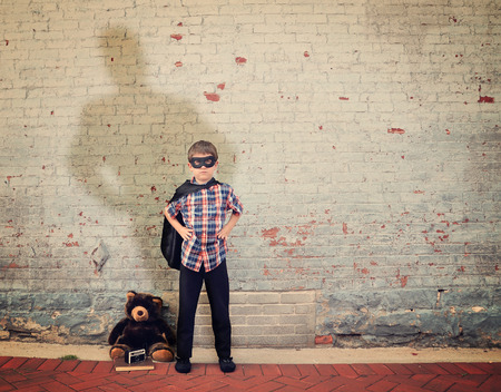 Photo pour A superhero boy is standing by an empty vintage brick wall with a cap and large shadow to represent strength, imagination or dream concept. - image libre de droit