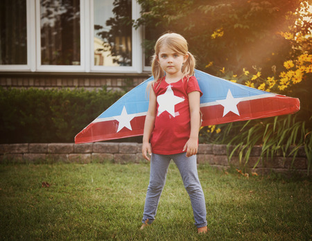 Foto de A little child is wearing homemade cardboard flying wings with stars on them pretending to be a pilot for a craft, imagination or exploration concept. - Imagen libre de derechos