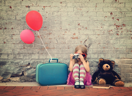 Foto de A photo of a vintage child taking a picture with an old camera against a brick wall with balloons and a teddy bear for a creativity or vision concept. - Imagen libre de derechos