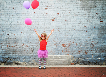 Photo for A little child is holding colorful balloons against a textured brick wall and waering sunglasses for a happiness or celebration conecpt. - Royalty Free Image