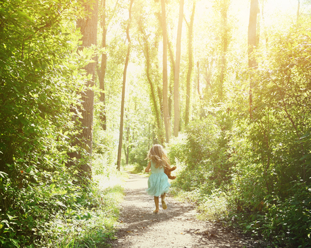 Photo pour A little child is running down a nature trail with sunlight on the trees for a happiness or freedom concept. - image libre de droit