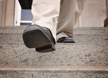 Photo pour A business man is stepping down the stairs at an office for a power, challenge or motivation concept. - image libre de droit