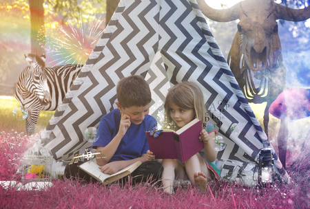 Foto de Little Children are reading an old story book in a teepee with purple grass and animals for an education or imagination concept. - Imagen libre de derechos