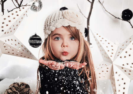 A young child is blowing white snowflakes in a studio background scene with stars and christmas ornaments for a holdiay concept.