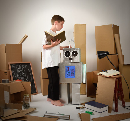 Foto de A child is reading a book and building a metal robot from cardboard boxes on white for an imagination, science or education concept. - Imagen libre de derechos