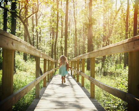 Photo for A little child is running on a wooden trail in the woods with trees with sunlight rays for a freedome or adventure concept. - Royalty Free Image