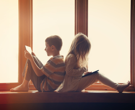 Foto de Two children are sitting by the window at home playing on their technology tablets with games and apps for a entertainment concept. - Imagen libre de derechos
