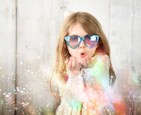 Photo pour A little child is wearing sunglasses and blowing magical rainbow glitter sparkles in the air for a celebration, happiness or party idea. - image libre de droit