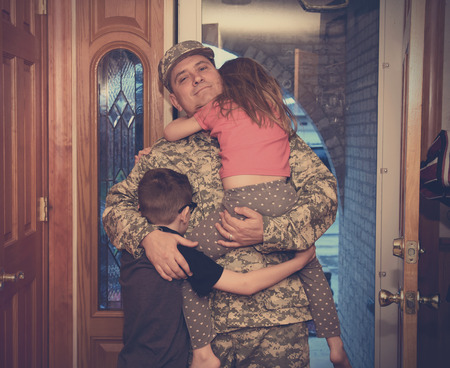 Photo for An army soldier man is coming home in the door and hugging his children for a love, family or reunited concept. - Royalty Free Image