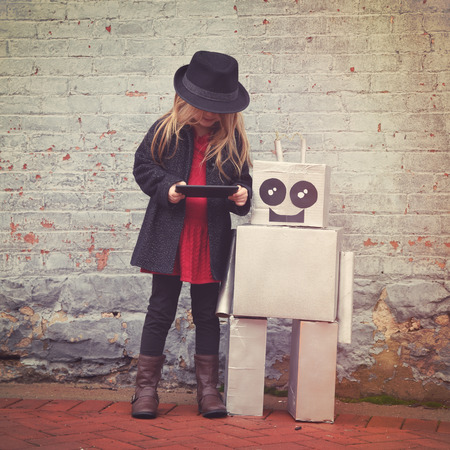 Foto de A little hipster child wearing a cool hat is holding a tablet with her toy robot friend downtown for a happiness or technology concept. - Imagen libre de derechos