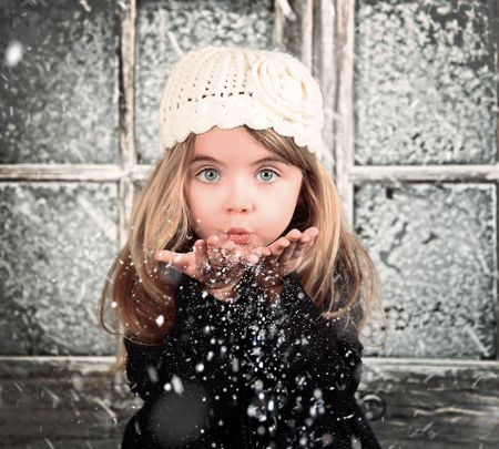 Foto de A young child is blowing white snowflakes in a winter background scene for a holiday christmas or season concept. - Imagen libre de derechos
