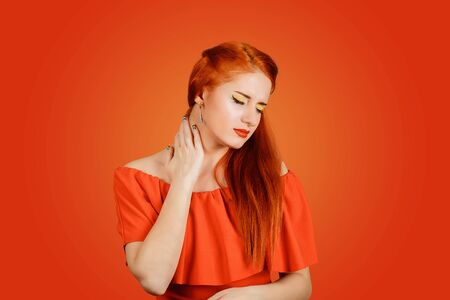Foto de Closeup of a girl having neck pain massaging it to relieve the ache isolated on a red background. Sick young woman having a sore throat - Imagen libre de derechos