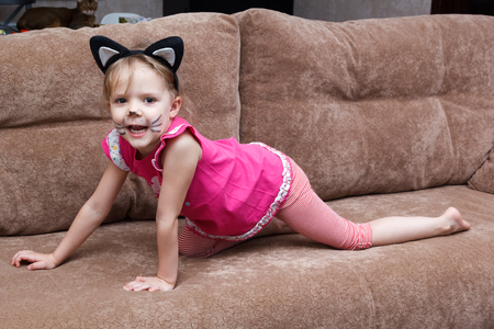 little girl with cat face painting on a couch