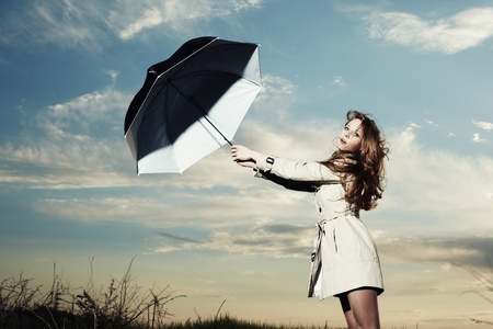 Fashion portrait of elegant woman in a raincoat on the nature. Woman with an umbrella