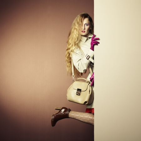 Foto de a young beautiful woman in a raincoat in interior. Conceptual fashion - Imagen libre de derechos