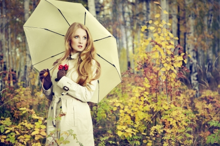 Fashion portrait of a beautiful young woman in autumn forest. Girl with umbrella
