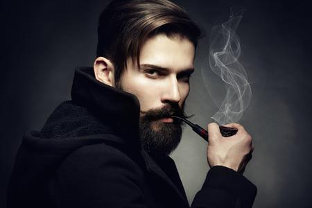 Foto de Artistic dark portrait of the young beautiful man  The young man smokes a tube  Close up - Imagen libre de derechos