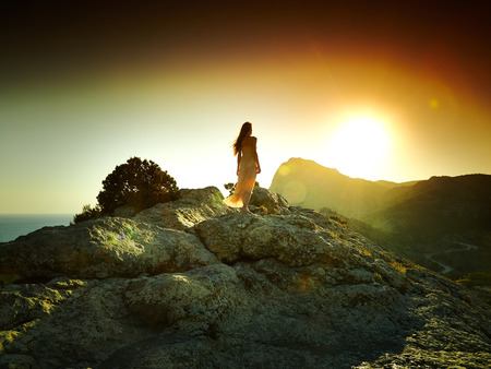 Photo pour Woman silhouette at sunset in mountains. Crimea landscape - image libre de droit