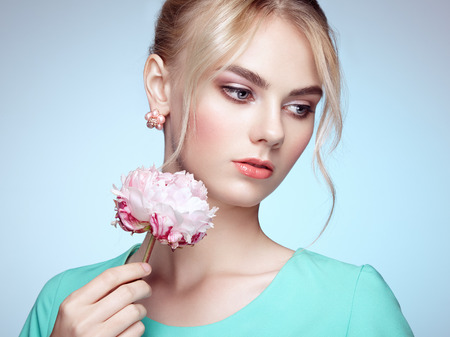 Portrait of beautiful sensual woman with elegant hairstyle.  Perfect makeup. Blonde girl. Fashion photo. Flowers