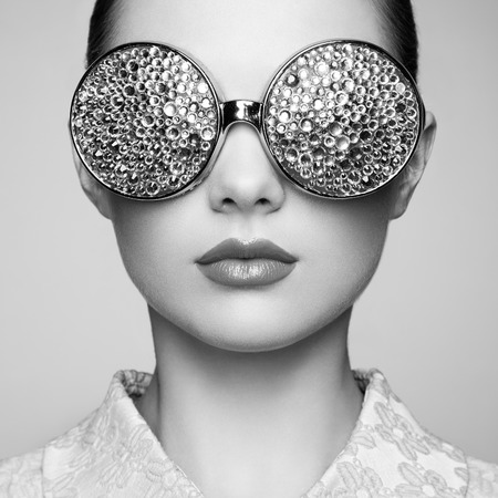 Photo pour Portrait of beautiful young woman with colored glasses. Beauty fashion. Perfect make-up. Colorful decoration. Jewelry. Black and white - image libre de droit
