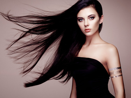 Photo for Fashion portrait of elegant woman with magnificent hair. Brunette girl. Perfect make-up. Girl in elegant dress. Flash tattoo gold - Royalty Free Image