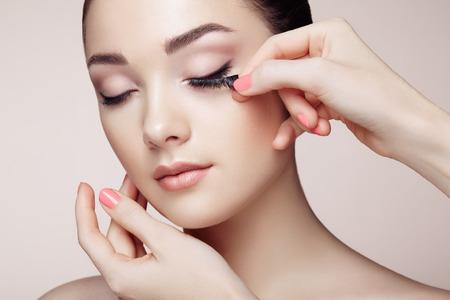 Photo for Makeup artist glues eyelashes. Beautiful woman face. Perfect makeup. Beauty fashion. Eyelashes. Cosmetic Eyeshadow - Royalty Free Image