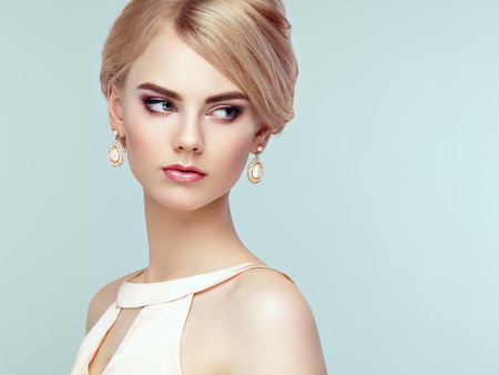 Foto de Portrait of beautiful sensual woman with elegant hairstyle.  Perfect makeup. Blonde girl. Fashion photo. Jewelry and dress - Imagen libre de derechos