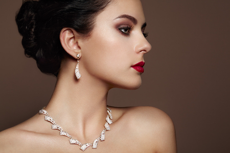 Foto de Fashion portrait of young beautiful woman with jewelry. Brunette girl. Perfect make-up.  Beauty style woman with diamond accessories - Imagen libre de derechos
