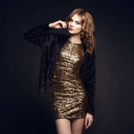 Photo pour Fashion portrait of elegant woman with magnificent hair. Blonde girl. Perfect make-up. Girl in gold dress on black background - image libre de droit