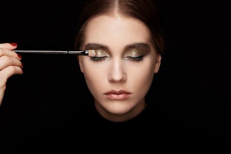 Foto de Makeup artist applies eye shadow. Beautiful woman face. Perfect makeup. Lips. Cosmetic Eyeshadow. Make-up detail. Eyeliner - Imagen libre de derechos