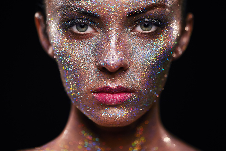 Foto de Portrait of beautiful woman with sparkles on her face. Girl with art make up in color light. Fashion model with colorful make-up - Imagen libre de derechos