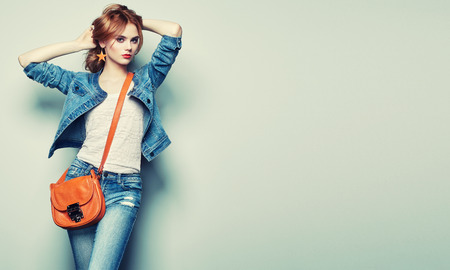Photo pour Fashion portrait of beautiful young woman with red hair. Girl in blouse and jeans. Jewelry and hairstyle. Girl with handbag - image libre de droit
